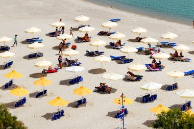 Beach with tourists, sun beds and umbrellas. Expected to be the