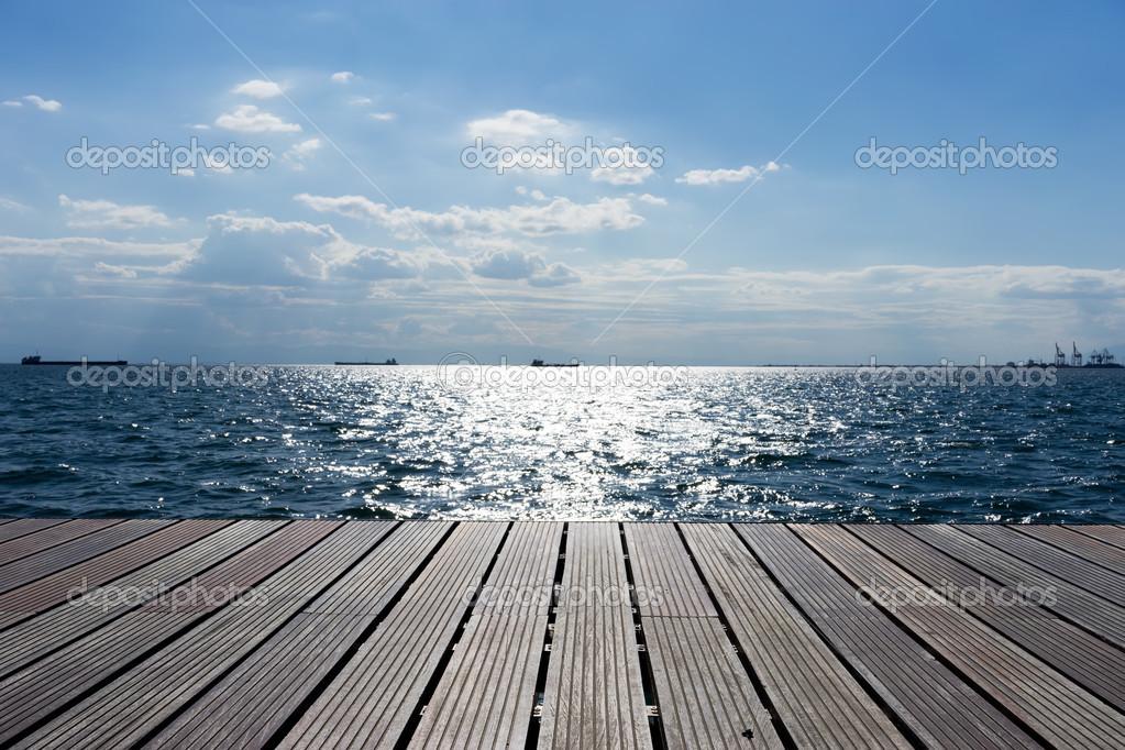 Wooden platform beside the ocean and blue sky