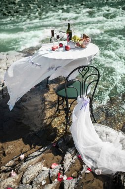 Decorated wedding table with chairs standing on the river