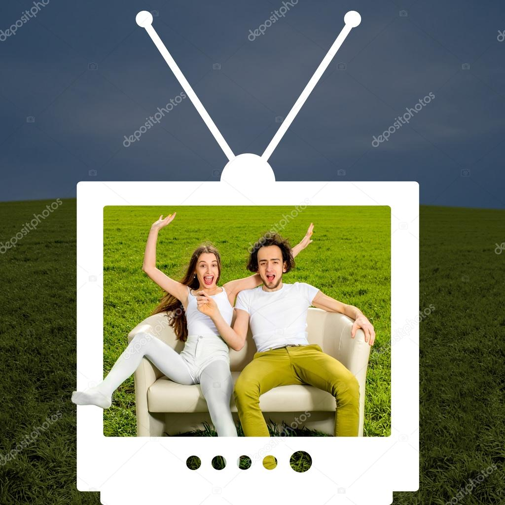 Crazy couple sitting on the couch in the green field looking thr