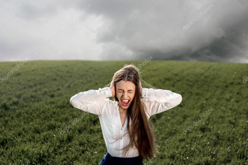 Woman crying in the field with cloudy sky