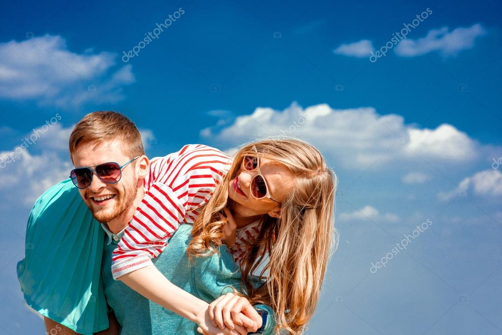 Happy couple embracing and having fun under the blue sky