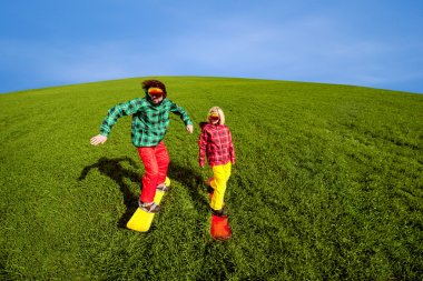 Young couple in sport wear snowboarding on the grass in the gree