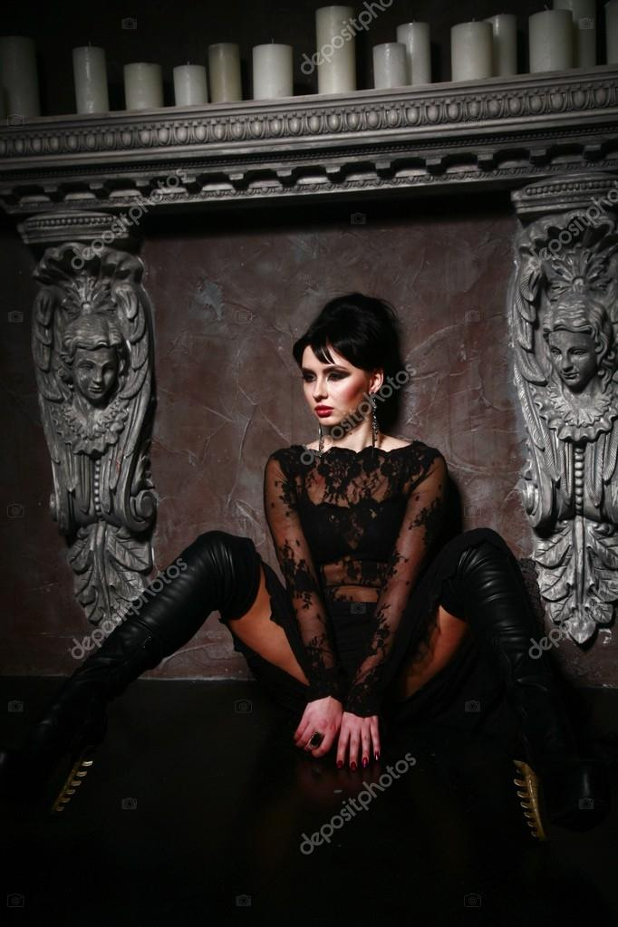 Gothic girl  sitting on the floor near the candels