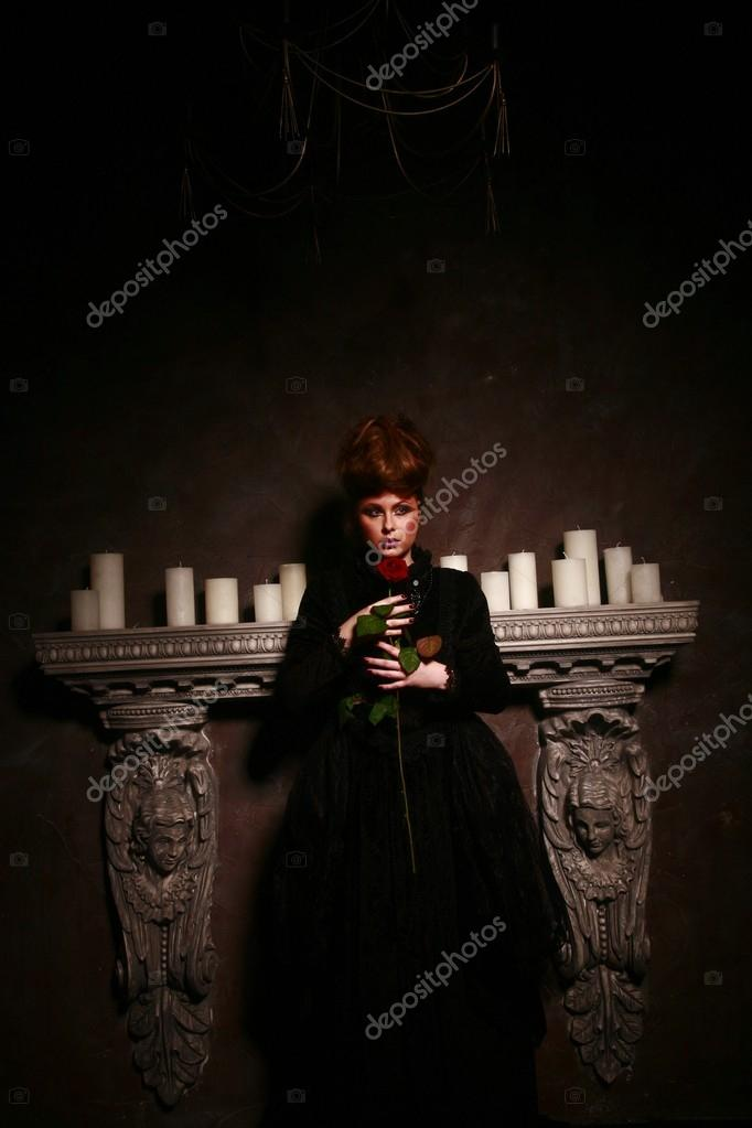 Gothic girl standing near candles with red rose
