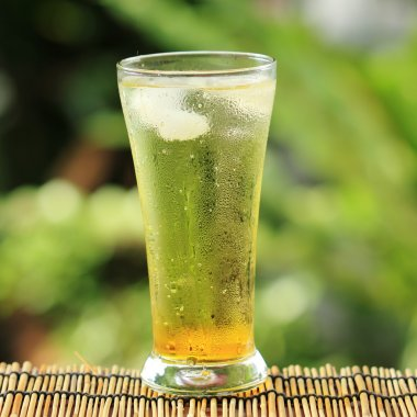 gold guarana soft drink with ice cubes