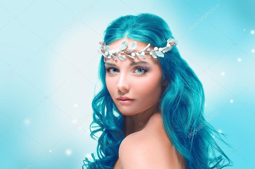 Beautiful girl with blue hair on a winter background