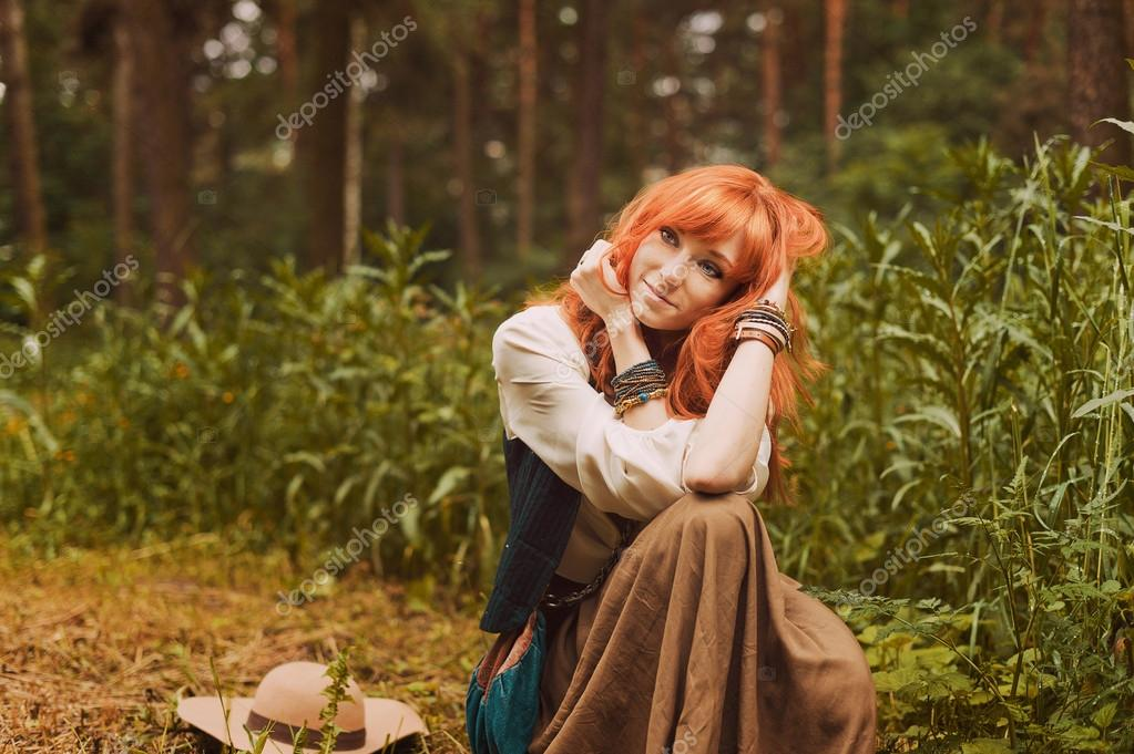 Portrait of romantic hippie woman smile in the woods.
