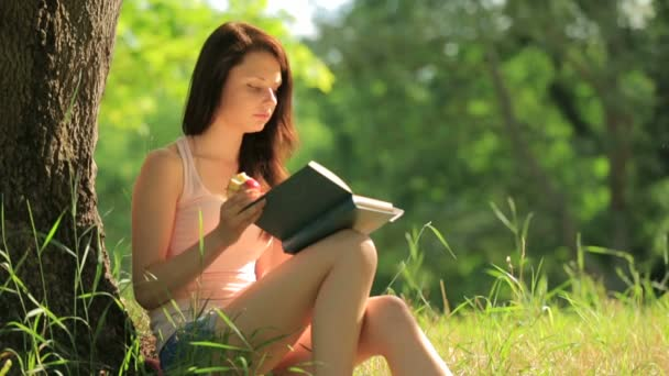 Girl sitting in park reading a book and eating an apple under tree