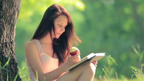 dívka sedící v parku, čtení knihy a jíst jablko pod stromem