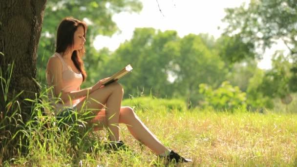 dívka sedící v parku, čtení knihy pod stromeček