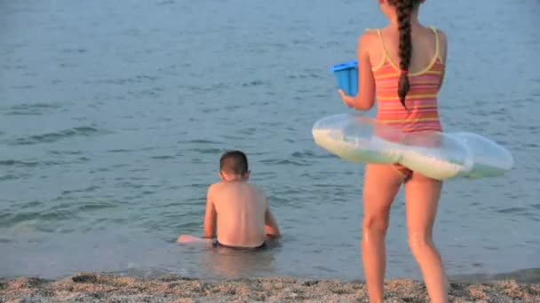 Little girl and boy playing in the sea