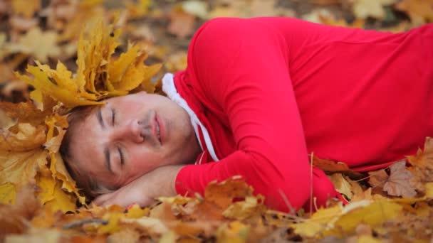Mann liegt auf Herbstlaub