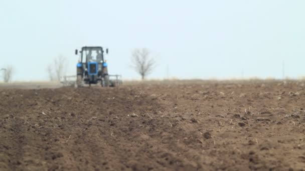 Farm tractor ploughing field before planting