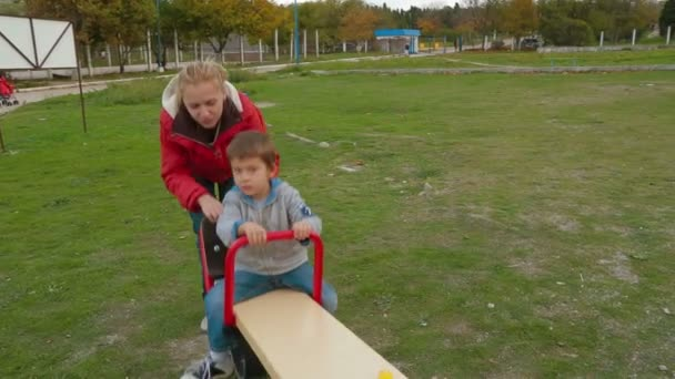 Two adults swinging little boy on playground.