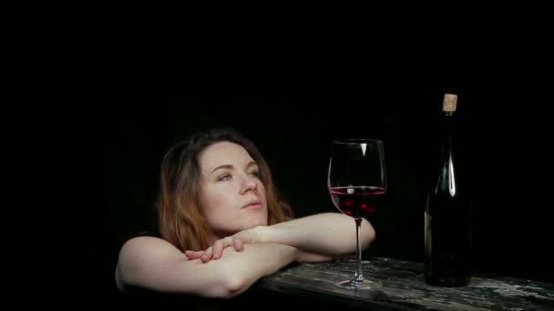 junge Frau blickt auf ein Glas Wein