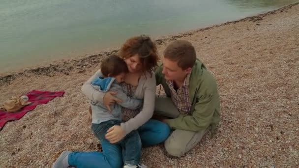 Happy family sitting on the beach