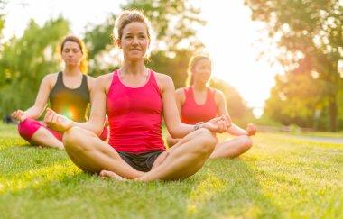 women doing yoga outdoors at sunset