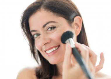 Attractive woman in her forties applying makeup