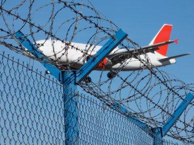 Landing airplane behind barbed wire