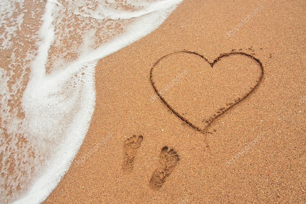Shape of the heart and footprints in the sand on the beach