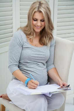 Beautiful pregnant woman sitting at home on chair, smiling and writing in pregnancy journal. Holding blue pencil and wearing blue watch.