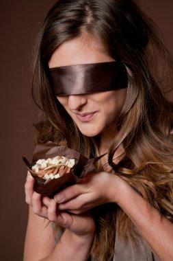 Blindfolded woman holding cake