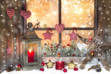 Red Christmas decoration with lantern on window sill with wood