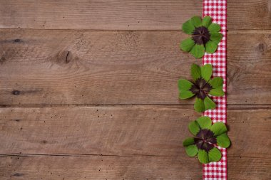 Wooden background with red and white checkered ribbon and green