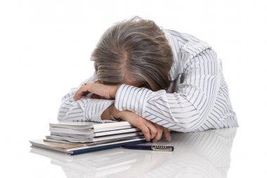 Overworked woman sleeping on books