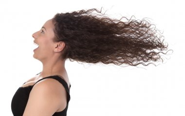 Windy: profile of laughing woman with blowing hair in wind isolated on white