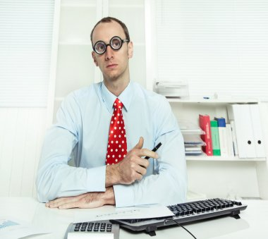Arrogant man sitting at desk with glasses, a red tie and a blue shirt