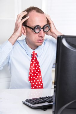 Shocked and stressed business man with lenses and a red tie at desk