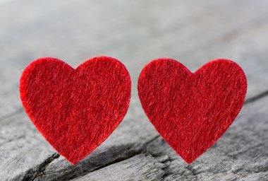 Two red hearts of felt on a wooden old shabby background.