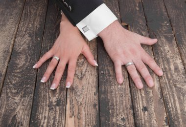 Wedding theme, man and woman hands on a wooden floor