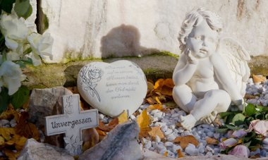 Grave with cross, heart and angels