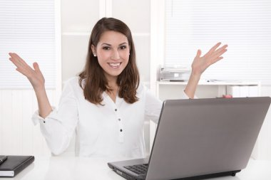 Woman in the office sitting on desk is happy with her work.