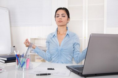Attractive secretary with closed eyes is doing meditation at off