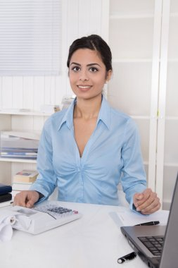 Young indian woman sitting at desk in her office.