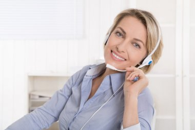 Satisfied mature businesswoman with headphone at office.