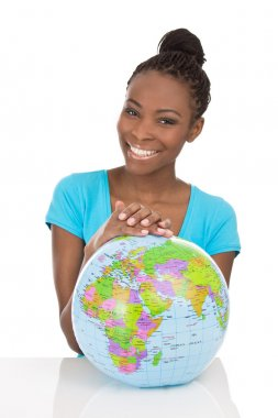 Isolated african american smiling woman sitting with globe in fr