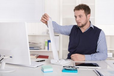 Young attractive accountant working with calculating machine.