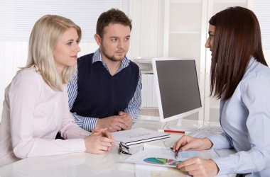 Young attractive couple at consultation with female consultant.
