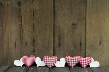 Checked hearts decorated on wooden board.