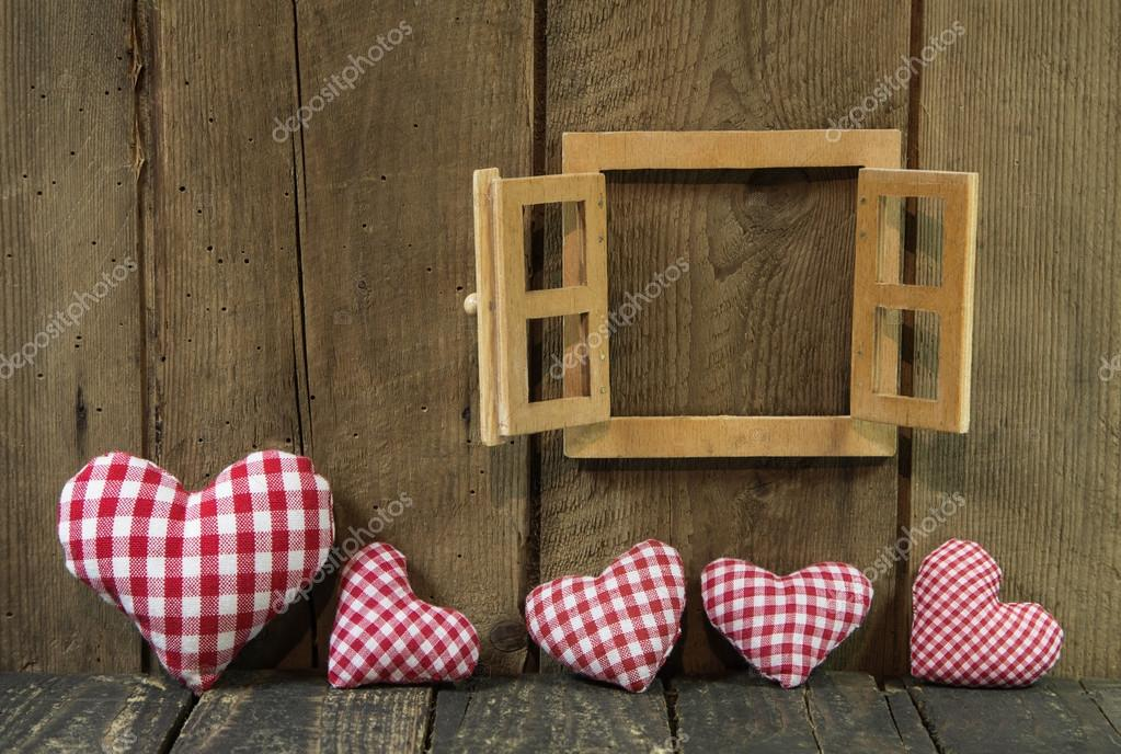 Checked hearts of fabric and wooden window frame.