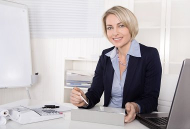Attractive happy older or senior business woman in the office.