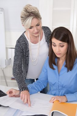 Senior business woman controlling a young sitting at desk.