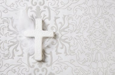 Mourning: white ceramic cross on grey ornament background.