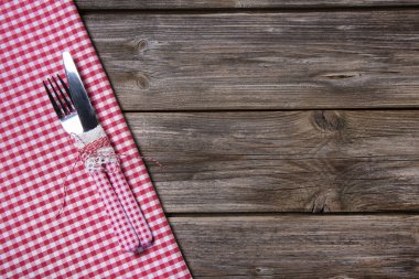 Knife and fork in red white checkered on wooden background.