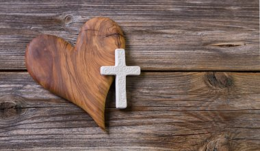 Wooden background with olive heart and white cross for an obitua